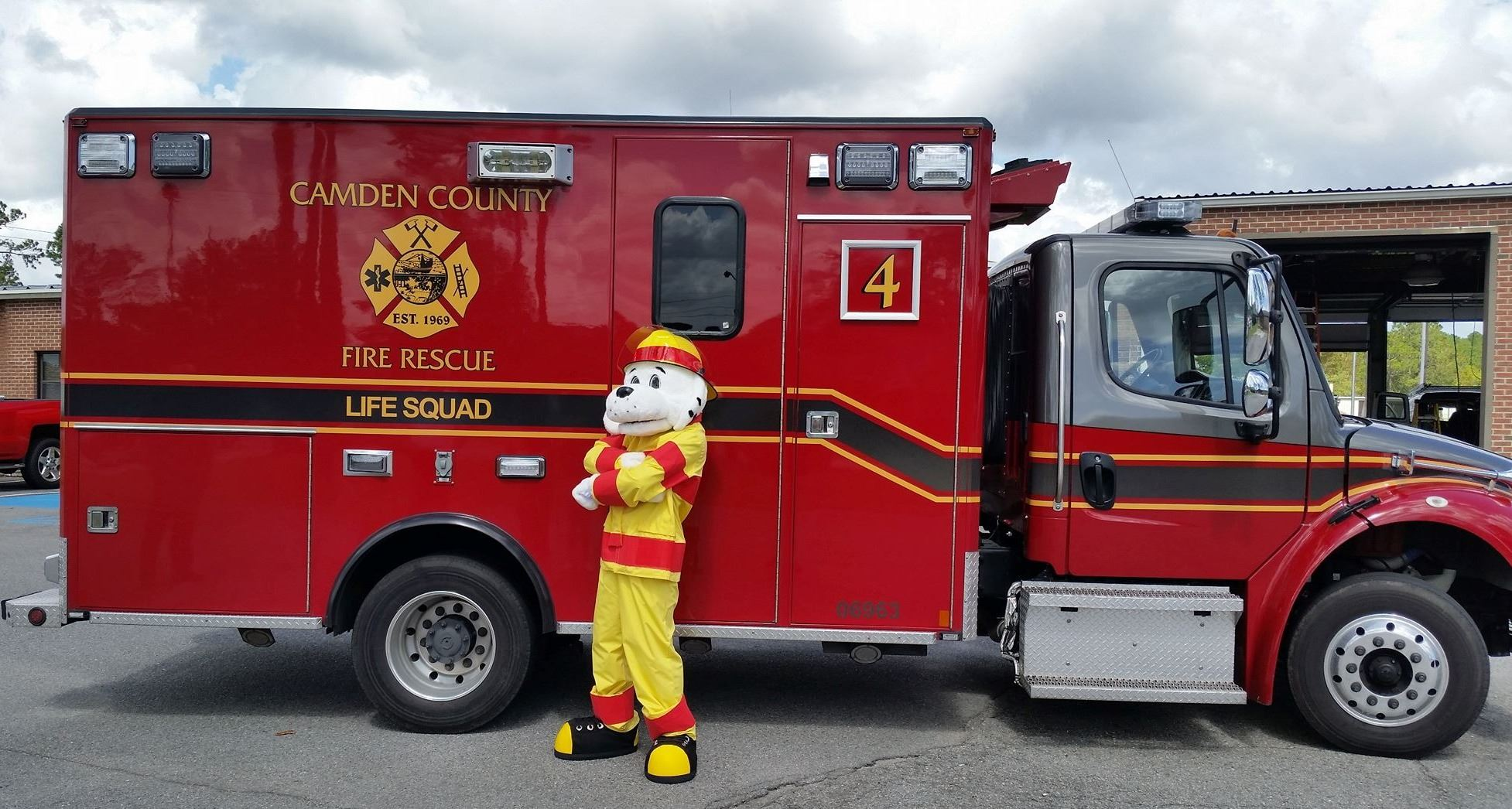 Sparky the Fire Dog standing in front of an ambulance